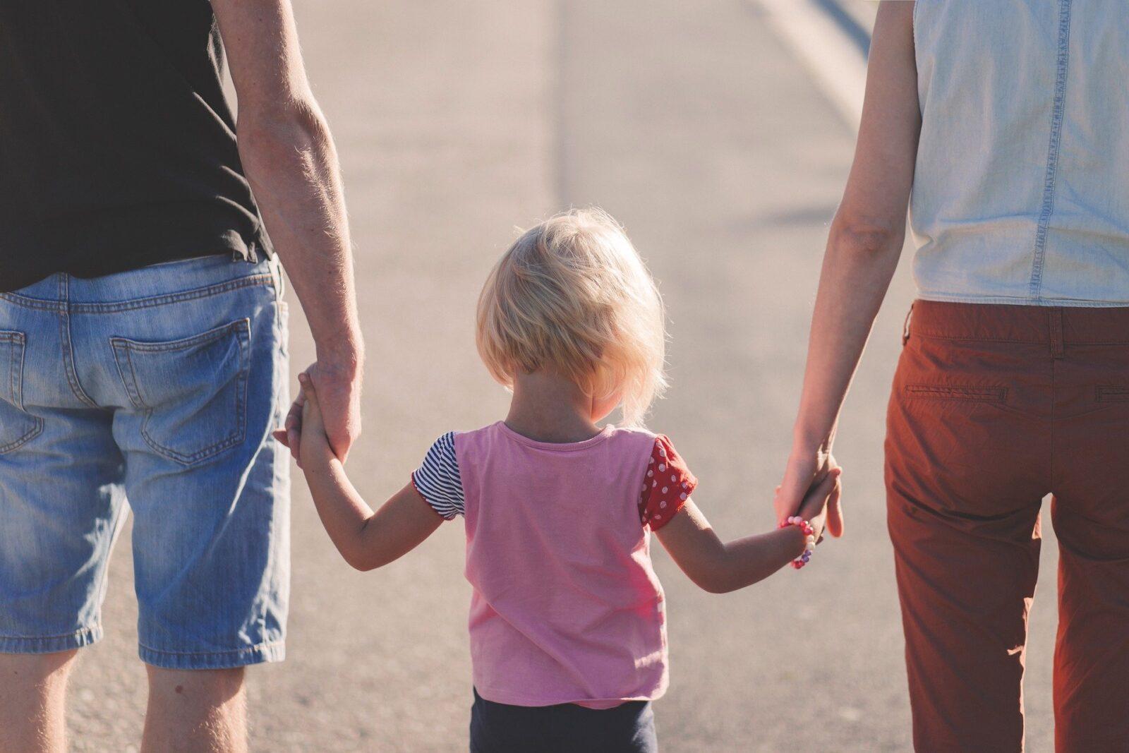 Kind geht Hand in Hand mit zwei Eltern